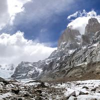 <strong>Rückweg über den Gletscher nach El Chalten. Links unter dem Breiten Felsgipfel dem Mocho befindet sich das Niponino. Rechts im Tal Fitz Roy in Wolken, die Poincenot und die<span>Aguja Rafael Juárez</span></strong>