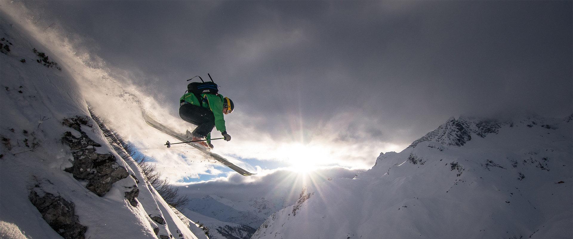 Drop über Cliff beim Freeriden mit Sonnenstrahlen im Hintergrund.