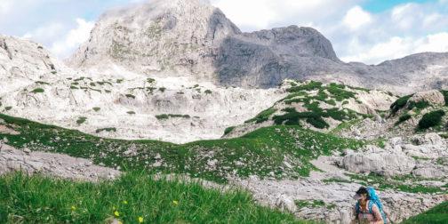 Wanderin im Steinernen Meer mit grüner Wiese und grauem Kalkfels im Hintergrund mit Wolken am Himmel