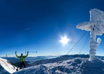 Thumbnail http://Skitourengeher%20am%20Gipfelkreuz%20bei%20Sonnenschein