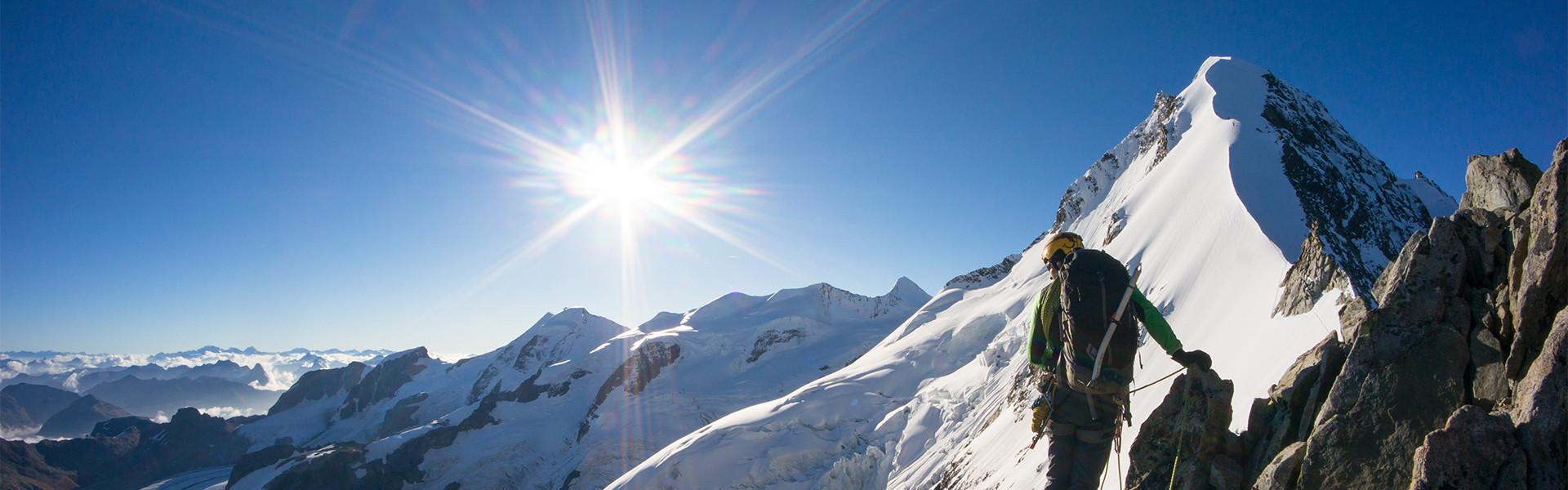 Bergsteiger bei Sonnenschein vor schneebedecktem Gipfel
