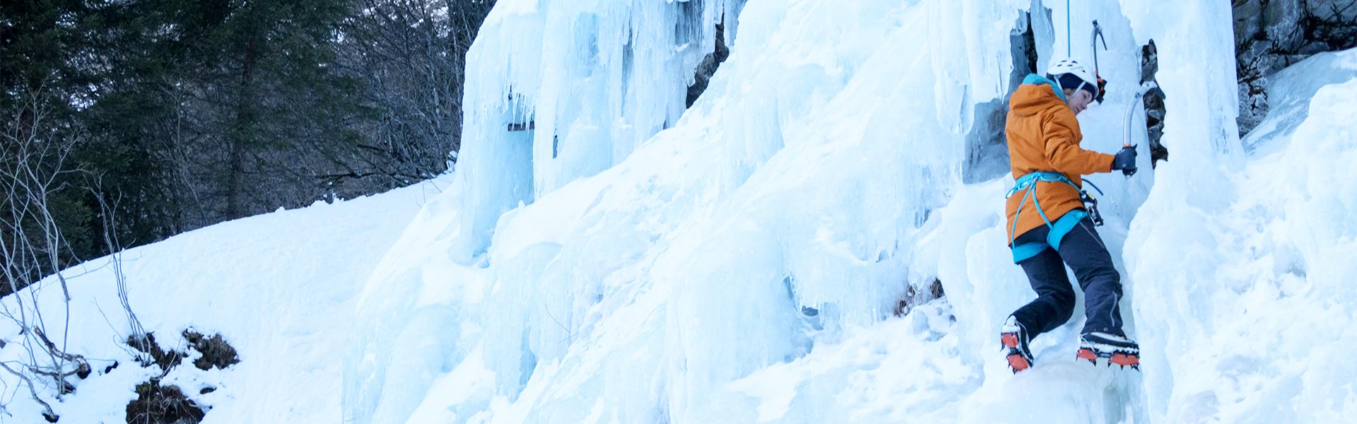 Frau probiert das Eisklettern gesichert im Nachstieg.