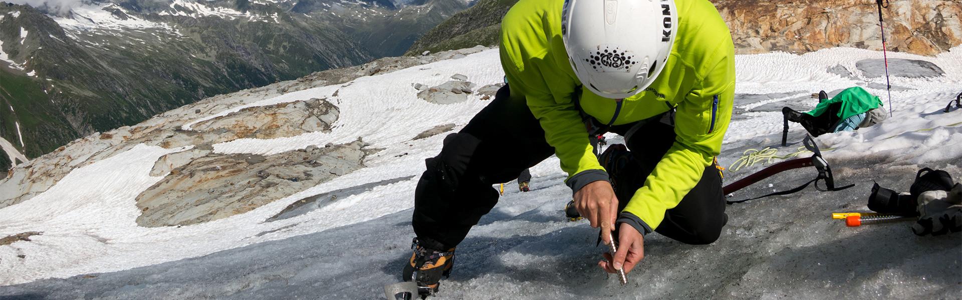 Bergsteiger mit Eisschraube auf Gletscher