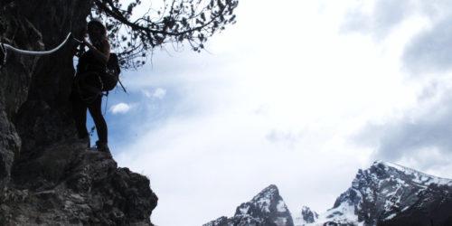Silvana Steinhöfel bei einem Klettersteig mit dem Watzmann, Hocheck und dem Kleinen Watzmann im Hintergrund