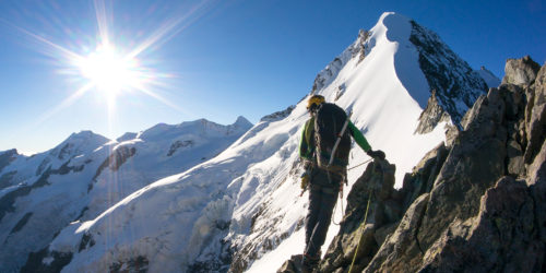 Bergsteiger im Sonnenschein vor schneebedecktem Gipfel