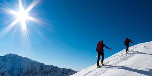 Zwei Skitourengeher im Aufstieg in verschneiter Winterlandschaft