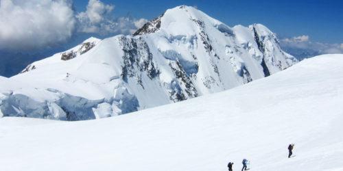 Drei Bergsteiger im Schnee auf dem Weg zum Gipfel