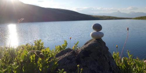 Steinmann übereinander mit Sonne und See in Balance und Ruhe