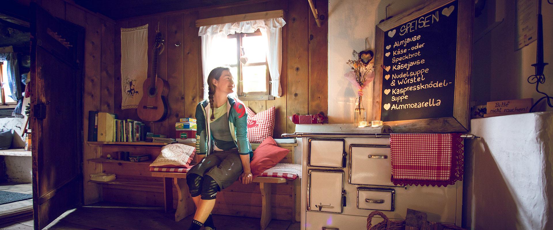 Radfahrerin in Almhütte vor Speißetafel und Radlkleidung in uriger Stube.