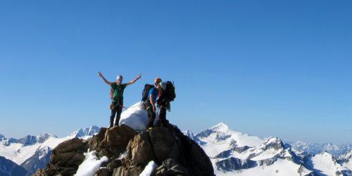 Drei Bergsteiger auf Gipfel