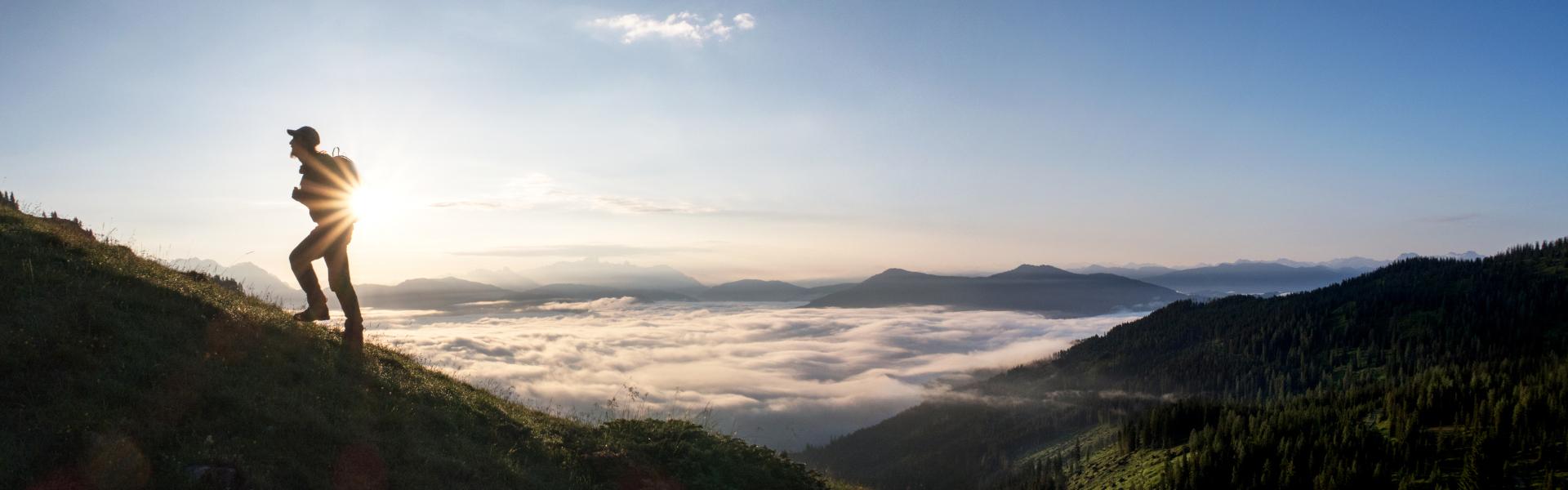 Wanderer bei Sonnenaufgang, Wolkendecke über Tal, Blauer Himmel