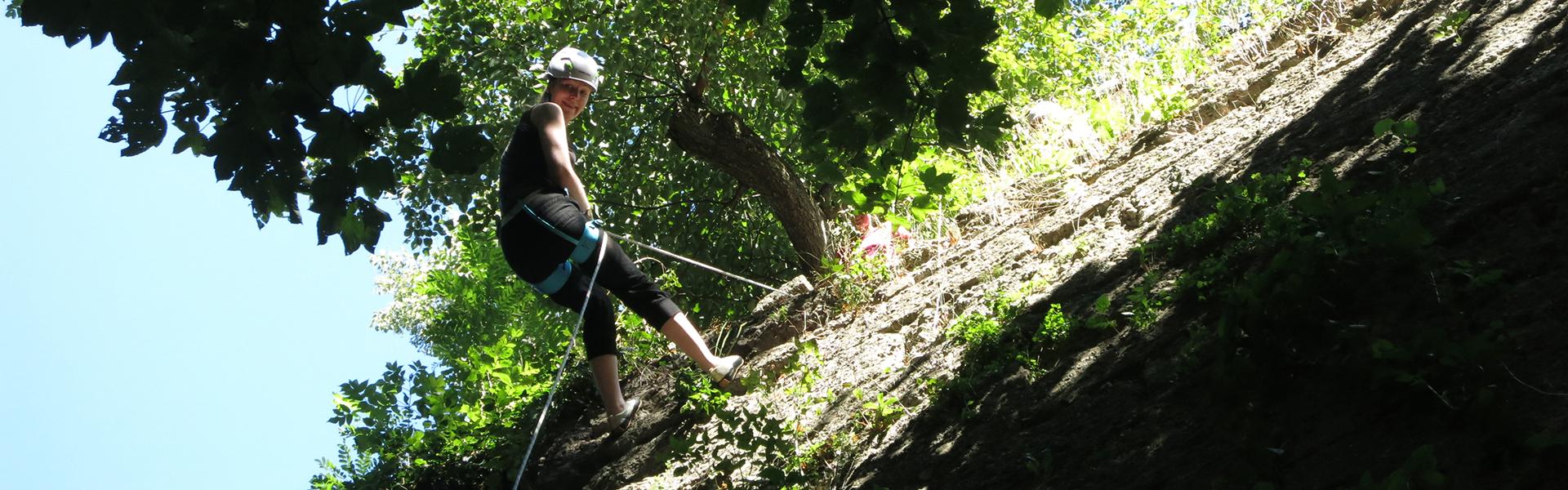 Frau beim Abseilen nach dem Klettern in der Natur