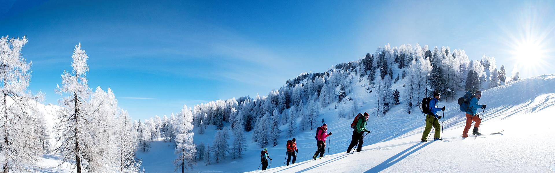 Skitourengruppe im Winter im Aufstieg mit Sonne und glitzerndem Schnee.