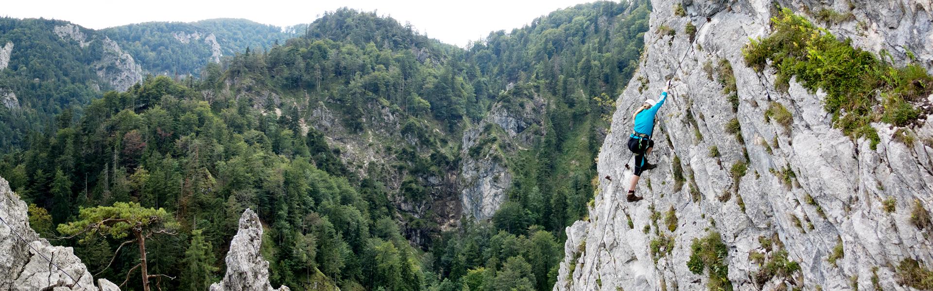 Klettersteiggeherin auf steiler Felswand