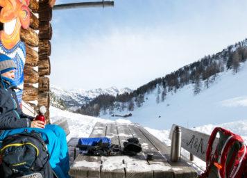 Thumbnail http://Skitourengeherin%20macht%20ras%20auf%20einer%20Holzhütte%20in%20Bergwelt%20mit%20Sonne%20im%20Gesicht