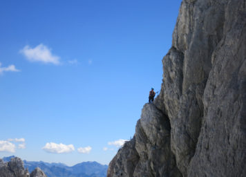 Thumbnail http://Klettersteiggeherin%20im%20Schultersteig%20am%20Dachstien%20mit%20Felswand%20und%20Panorama