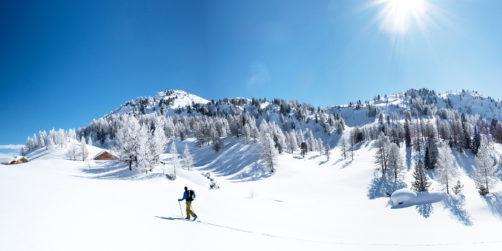 Skitourengeher mit traumhaften Panorama und weite Winterlandschaft bei Sonnenschein