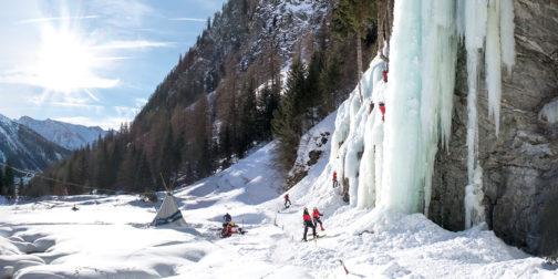 Eiskletterer klettern im Eiskletterpark in Osttirol mit strahlender Sonne und blauen Eisformationen.